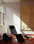 Glazed terra-cotta vases beside black designer lounger on red lacquered wood flooring