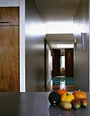 Pumpkins and mangos on a table in front of an open, ceiling height hallway
