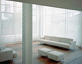 White sectional sofa and matching ottomans in front of a transparent curtain in front of window in a former factory building