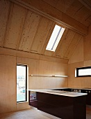 Open kitchen with counter and dark wood cabinets in a converted attic with bright wood paneling and assorted windows