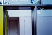 View through a glass facade into a hallway with a built-in wardrobe