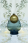 A golden Christmas tree bauble in a vase