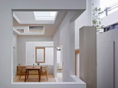 Simple table and chairs in Bauhaus style in a modern house with cut-outs in the wall and ceiling