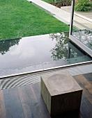Stool made of solid wooden cube in front of open terrace door and wet terrace floor