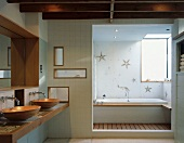 Washstand with wooden sinks and doorway to bathtub with starfish-patterned tiles