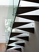 Back of made-to-measure steel staircase with glass balustrade and spotlights in wall