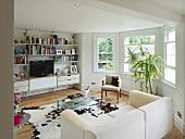 Modernes Wohnzimmer mit traditionellen Erkerfenstern und Kuhfell vor weißem Sofa