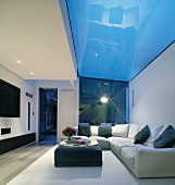 Comfortable, upholstered sofas with cushions in modern living room with glass ceiling panel