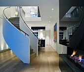 Modern, open-plan living space with curved staircase and fireplace