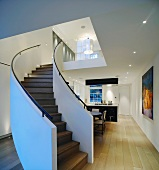 Curved staircase with view of designer ceiling lamps and open-plan kitchen-dining area with light floorboards