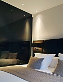 Cushions on double bed with upholstered head next to black, reflective wall