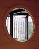 View through a bull's eye in a wooden facade of a louvered window