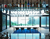 Bar with liquor and glasses on suspended shelves and view of a dining table in front of a glass facade