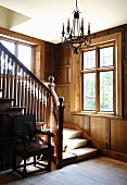 Wooden stairs and banister in a traditional home with wood paneling on the wall