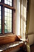 Custom upholstered window seat with leaded window