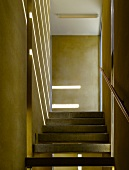 Strip lighting on a yellow wall and concrete steps in a narrow stairway