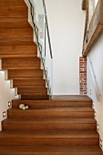 Back view of a wooden staircase in a renovated stairwell with recessed wall lighting