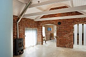 Living room in a converted barn with brick wall and openings with round arches under a white lacquered wood ceiling an wood burning stove