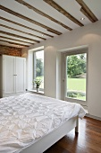 Bedroom in a renovated house with old wood beams and suspended ceiling and terrace door with a garden view