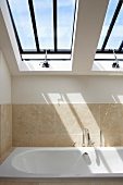 Modern bathroom under a pitched roof with skylights above a bathtub
