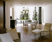 Open living room with white leather lounger in front of a dining table with chairs and a view of the terrace