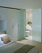 Modern, white bedroom with open glass door and view into a bathroom ensuite