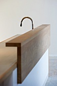 Kitchen counter clad in wood in front of a sink and faucet