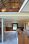Former barn with freestanding kitchen counter under a mezzanine with white metal supports