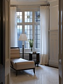 View through an open door of a chaise lounge upholstered in white leather in Art Deco style in front of leaded windows
