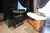 Freestanding bathtub clad in copper colored material in front of black, glossy cabinet on a tiled floor