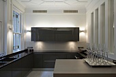 Counter with champagne glasses on a tray in a designer kitchen with brown, glossy cabinets in a stately home