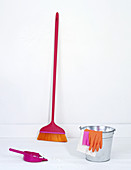 A zinc bucket, rubber gloves, a broom and a dustpan and brush