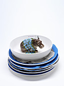 A stack of plates lined with felt with a hippo figurine in the bowl on the top