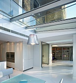 Open living room in a modern extension with glass roof and steel construction