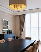 Dark dining table with upholstered chairs under a hanging lamp with a gold shade in front of a window