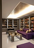 Living room with purple sofa in front of a library wall and indirect lighting under an open ceiling