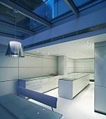 In Abendstimmung getauchter Essplatz unter Glasdach vor cooler Designerküche in Weiss