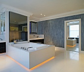 Bathtub for two with yellow back lighting in the floor area in the spacious bathroom