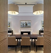 View through open double doors of dining table with upholstered chairs and designer pendant lights in dining room