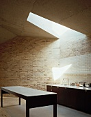 Open minimalist kitchen in front of a brick wall and skylight