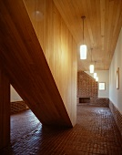 Entry hall with terra-cotta floor and wooden enclosed stairwell