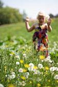 Little girl running through a summer meadow