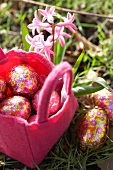 Chocolate Easter eggs in a pink felt basket in a meadow