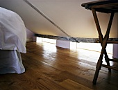 Sleeping area under a pitched roof and old wooden floor