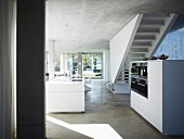 Open living room with concrete ceiling and floor and white free standing kitchen unit in front of a stairway