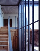 Stairway with rustic, wooden stairway in front of a glass and steel facade