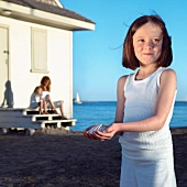 Young Girl Holding Shell at the Beach; Beach House