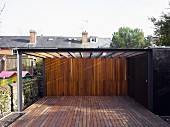 Pergola above a contemporary wood patio going over a wall