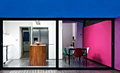 View through spacious patio window in illuminate living-dining room with pink wall