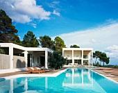 Pool in front of contemporary white villa in a Mediterranean landscape